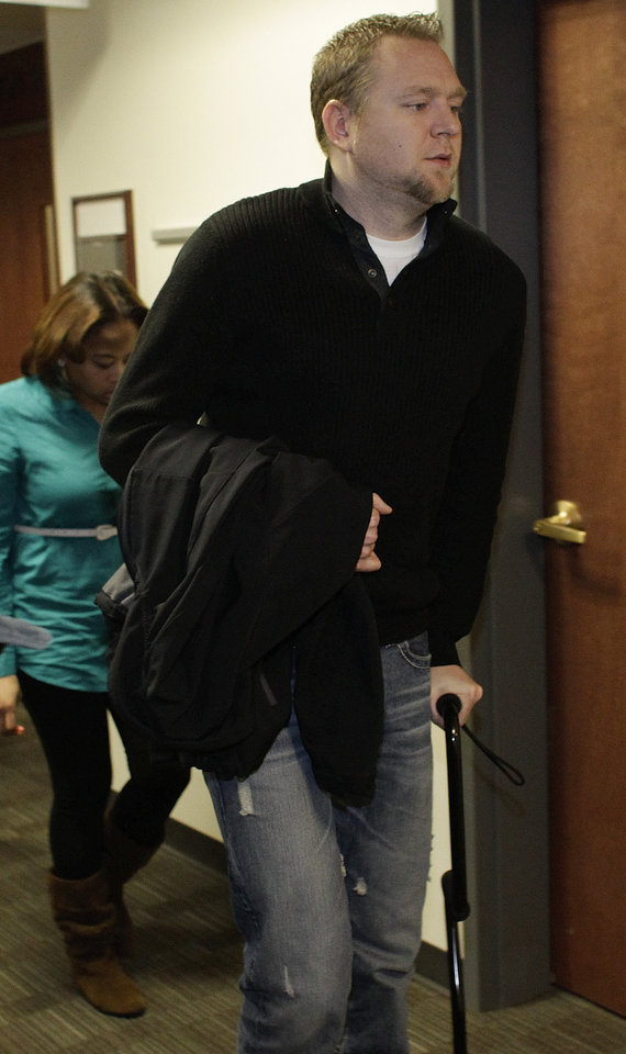 Josh Nolan, a single father of two who was shot in the leg and in the arm at the theater uses a cane as he leaves a court proceeding for Aurora theater shooting suspect james Holmes at the courthouse in Centennial, Colo., on Friday, Jan. 11,  2013.  The judge granted a defense motion to delay the arraignment of Holmes until March 12. The decision comes a day after the judge ruled that Holmes should stand trial.  (AP Photo/Brennan Linsley)