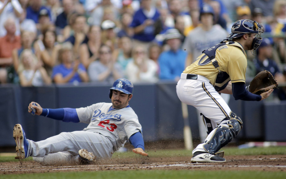 Photo - Los Angeles Dodgers' Adrian Gonzalez, left, scores off of a RBI hit against the Milwaukee Brewers during the fifth inning of a baseball game Sunday, Aug. 10, 2014, in Milwaukee. (AP Photo/Darren Hauck)