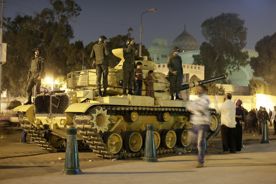 An Egyptian protester takes a picture with his mobile of his children on top of an Egyptian army tank outside the presidential palace, background, in Cairo, Egypt, Saturday, Dec. 8, 2012. Egypt's military warned Saturday of 'disastrous consequences' if the crisis that sent tens of thousands of protesters back into the streets is not resolved, signaling the army's return to an increasingly polarized and violent political scene.(AP Photo/Hassan Ammar)