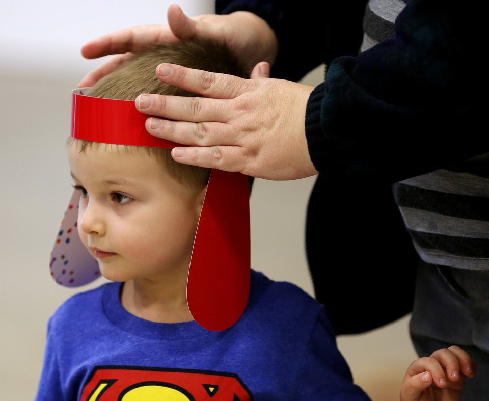 Court Van Dyne, 3, gets help putting on Clifford ears during a birthday party for Clifford the Big Red Dog on Saturday. Photo by Bryan Terry, The Oklahoman <strong>BRYAN TERRY - THE OKLAHOMAN</strong>