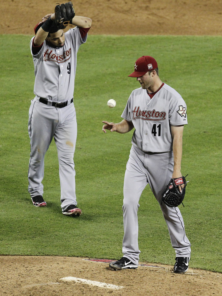 Photo -   Houston Astros' Jordan Lyles (41) tosses the ball in the air and teammate Marwin Gonzalez (9) takes his cap off to wipe sweat away during a seven-run sixth inning for the Arizona Diamondbacks in a baseball game on Sunday, July 22, 2012, in Phoenix. (AP Photo/Ross D. Franklin)