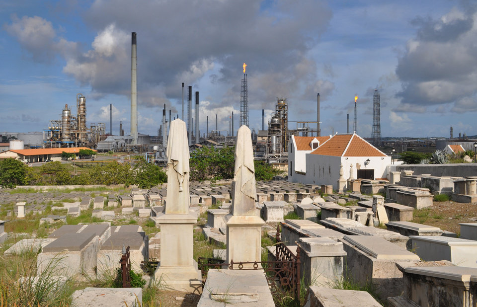 In this Nov. 12, 2012 photo, a portion of the Beth Haim cemetery, backdropped by the Isla oil refinery, is seen in Blenheim, on the outskirts of Willemstad, Curacao. Beth Haim, believed to be one of the oldest Jewish cemeteries in the Western Hemisphere, established in the 1950s and considered an important landmark on an island where the historic downtown has been designated a UNESCO World Heritage Site, is slowly fading in the Caribbean sun. Headstones are pockmarked with their inscriptions faded, stone slabs that have covered tombs in some cases for hundreds of years are crumbling into the soil, marble that was once white is now grey, likely from the acrid smoke that spews from the oil refinery that looms nearby. (AP Photo/Karen Attiah)