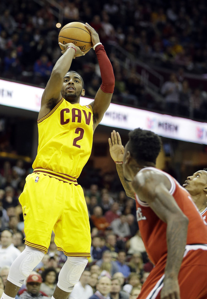 Photo - Cleveland Cavaliers' Kyrie Irving (2) shoots over Milwaukee Bucks' Larry Sanders, foreground, in the fourth quarter of an NBA basketball game Friday, Jan. 25, 2013, in Cleveland. Irving scored 35 points to lead the Cavaliers to a 113-108 win. (AP Photo/Mark Duncan)