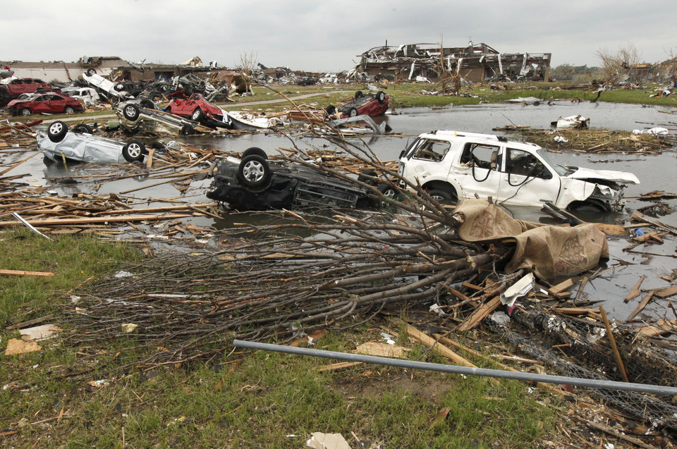 Photo - Cars destroyed by the May 20th tornado were tossed into the pond  near Briarwood School in Moore, OK, Saturday, May 25, 2013,  Photo by Paul Hellstern, The Oklahoman