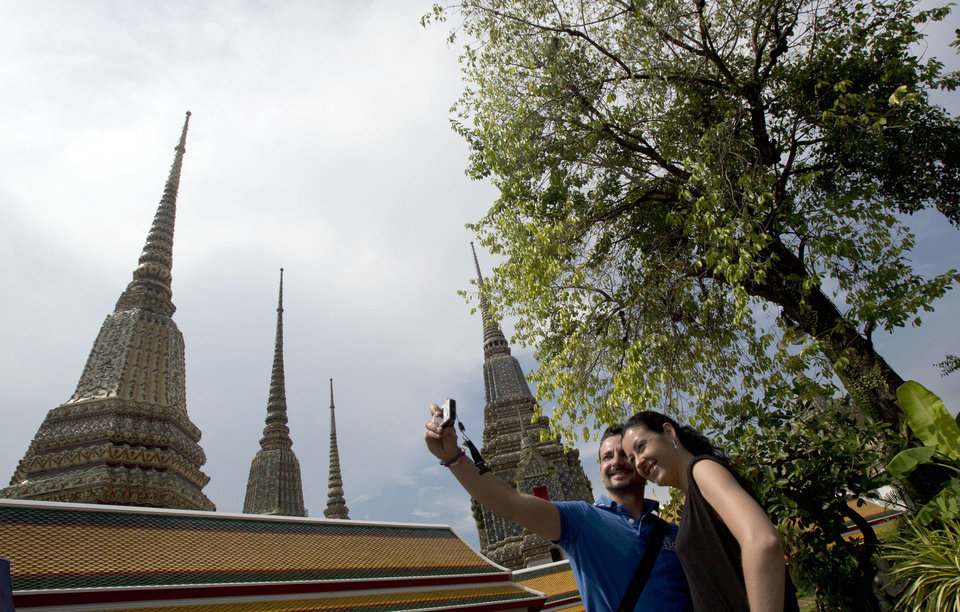 Photo - A couple of Western tourists snap a souvenir photo at a Wat Pho temple in Bangkok, Thailand Tuesday, May 27, 2014. The drama of Thailand's military takeover has played out mainly in the political arena. While the army detains political leaders and issues stern warnings on TV, tourists are kicking back on the country's famed beaches and sightseeing in Bangkok. The main impact on visitors for now is a 10 p.m. curfew, which forces nightlife to close four hours earlier. (AP Photo/Sakchai Lalit)