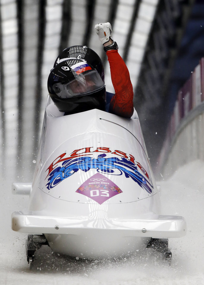 The team from Russia RUS-1, piloted by Alexander Zubkov and brakeman Alexey Voevoda, brake after their third run during the men's two-man bobsled competition at the 2014 Winter Olympics, Monday, Feb. 17, 2014, in Krasnaya Polyana, Russia. (AP Photo/Dita Alangkara)