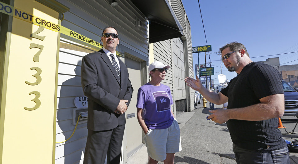 Photo - Cannabis City owner James Lathrop, right, talks with Deb Greene, who is first in line at the store on the first day that sales of recreational pot is legal in the state Tuesday, July 8, 2014, in Seattle. At left is security guard Dan Weber. The shop is the first and, initially, only store in Seattle to legally sell pot. (AP Photo/Elaine Thompson)