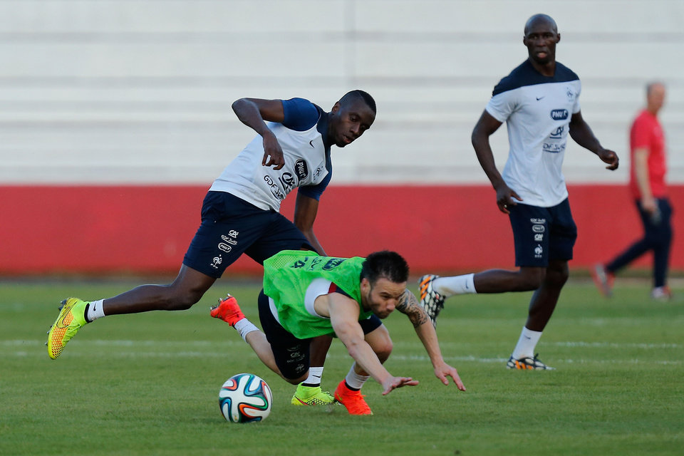Photo - French forward Mathieu Valbuena, down, is fouled by Blaise Matuidi, left, during the first training session of the French national soccer team at the Santa Cruz Stadium in Ribeirao Preto, Brazil, Tuesday, June 10, 2014. France will face Ecuador, Switzerland and Honduras in group E of the 2014 Soccer World Cup. (AP Photo/David Vincent)