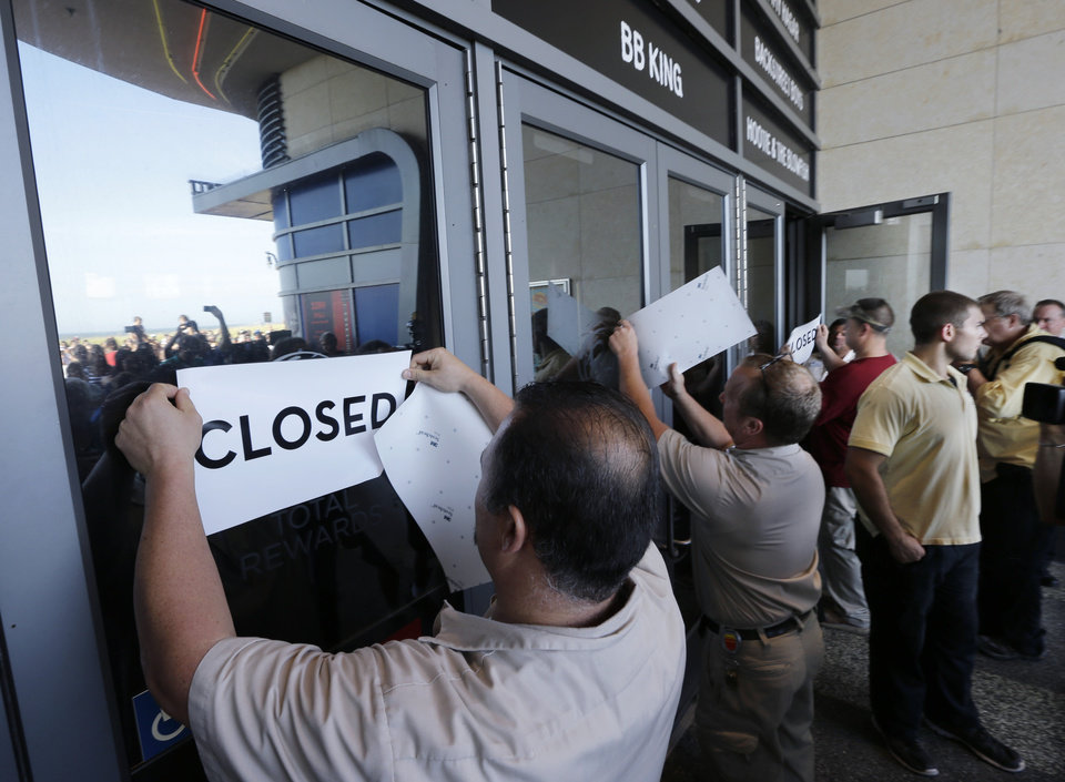 Photo - Workers put closed signs on the entrance of the Showboat Casino Hotel Sunday, Aug. 31, 2014, in Atlantic City, N.J. The show is ending for the Showboat Casino Hotel in Atlantic City. The Mardi Gras-themed casino is shutting down at 4 p.m. Sunday after 27 years on the Boardwalk. Owner Caesars Entertainment is closing the still-profitable Showboat to reduce the number of casinos in Atlantic City, which has been struggling with plunging revenue and increased competition. (AP Photo/Mel Evans)