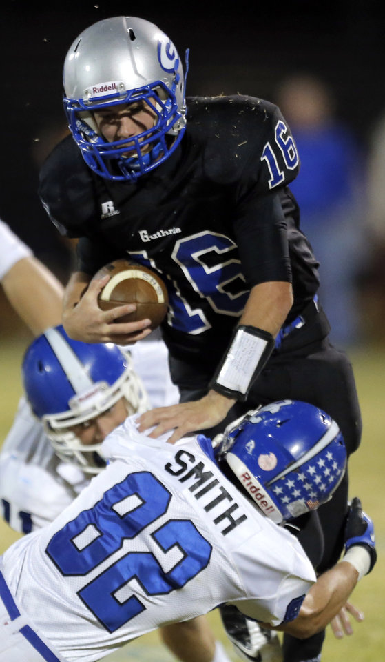 Photo - Deer Creek's Jackson Smith tackles Guthrie's Bryan Dutton during the high school football game between Guthrie and Deer Creek at Guthrie, Thursday, Oct. 18, 2012. Photo by Sarah Phipps, The Oklahoman