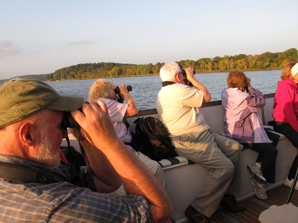 Photo - In this October 5, 2013 photo, birders and tourist watch aboard the boat