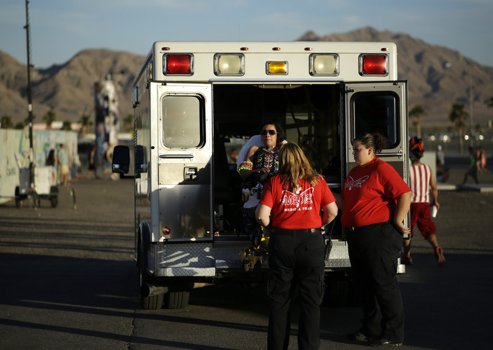Photo - A woman is loaded in to an ambulance outside of the Las Vegas Motor Speedway on the first night of the Electric Daisy Carnival, Friday, June 20, 2014, in Las Vegas. Between Friday evening and Sunday morning, Las Vegas police reported 560 mostly minor medical calls, with 17 resulting in trips to the hospital. (AP Photo/John Locher)