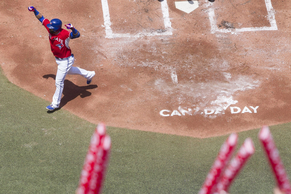 Photo - Toronto Blue Jays' Jose Bautista celebrates after hitting a solo homer off Milwaukee Brewers pitcher Marco Estrada during first inning interleague baseball action in Toronto on Tuesday July 1 , 2014. (AP Photo/The Canadian Press, Chris Young)