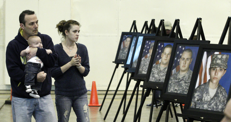 Jeff Archer, left, of Duncan, Okla., holding four-month old Cole Jones, walks with Janeen Jones, right, of Norman, Okla., past a display of photographs of some of the 14 Oklahoma National Guard soldiers who have died during the deployment of the 45th Infantry Brigade deployment to Afghanista and Kuwait, before the welcome home ceremony for 130 members of the group, in Oklahoma City, Saturday, March 3, 2012. (AP Photo/Sue Ogrocki) ORG XMIT: OKSO103