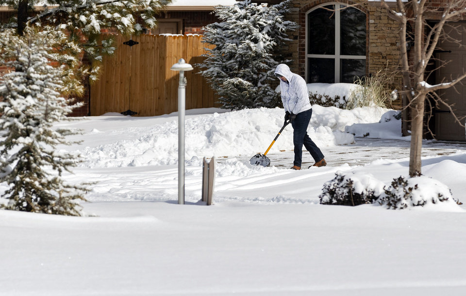 Photo - A person works to shovel snow from the driveway in Yukon, Okla. on Wednesday, Feb. 17, 2021.  [Chris Landsberger/The Oklahoman]