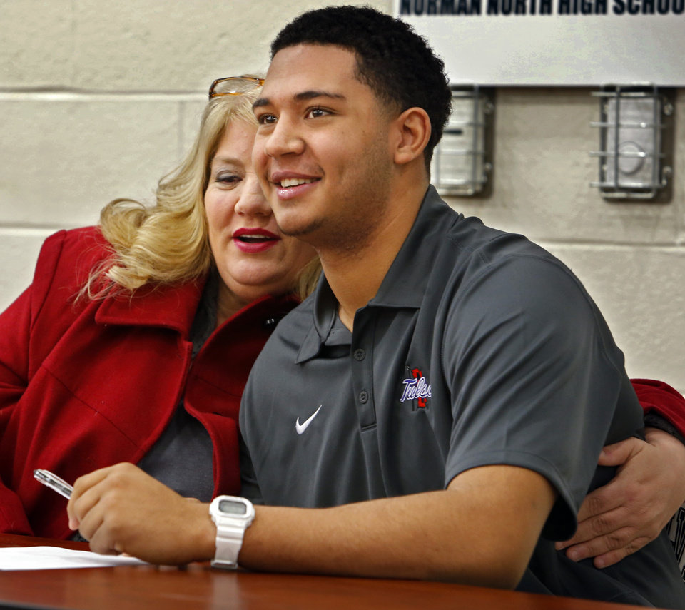 Photo - Tulsa University football signee Payton Prince sits with his mother Michele Prince at signing day ceremonies at Norman North High School on Wednesday, Feb. 5, 2014 in Norman, Okla.  Photo by Steve Sisney, The Oklahoman