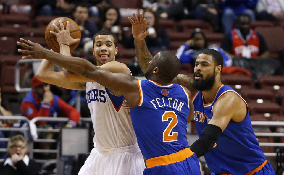 Photo - Philadelphia 76ers' Michael Carter-Williams, left, tries to keep the ball away from New York Knicks' Raymond Felton, center, and Tyson Chandler during the first half of an NBA basketball game, Friday, March 21, 2014, in Philadelphia. (AP Photo/Matt Slocum)