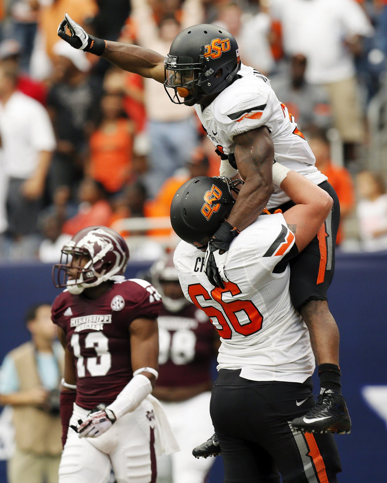 Oklahoma State's Jeremy Smith (31) and Travis Cross (66) celebrate a touchdown run by Smith in the fourth quarter near Mississippi State's Cedric Jiles (13) during the AdvoCare Texas Kickoff college football game between the Oklahoma State University Cowboys (OSU) and the Mississippi State University Bulldogs (MSU) at Reliant Stadium in Houston, Saturday, Aug. 31, 2013. OSU won, 21-3. Photo by Nate Billings, The Oklahoman