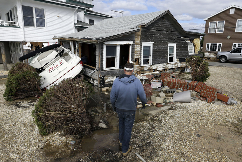 Michael Martin looks at his neighbor's house that was heavily damaged by surge from Superstorm Sandy on Cedar Bonnet Island, N.J., Saturday, Nov. 3, 2012. (AP Photo/Patrick Semansky) ORG XMIT: NJPS107