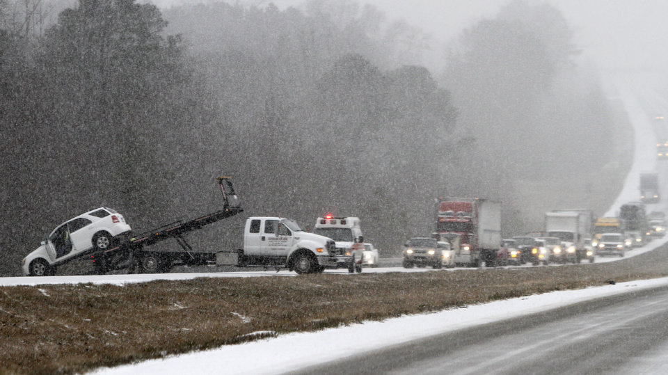 Photo - Traffic backs up as a wrecker pulls a car out of a ditch on I-65 during an unual snow Tuesday, Jan. 28, 2014, in Clanton, Ala.   A rare storm left a slippery layer of ice and snow across a region unaccustomed to dealing with the wintry threat. (AP Photo/Butch Dill)