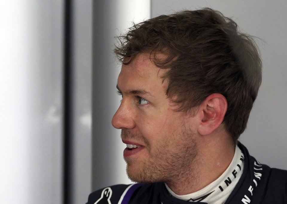 Photo - Red Bull driver Sebastian Vettel of Germany talks to a crew member in his team garage during the first practice session for Sunday's Malaysian Formula One Grand Prix at Sepang International Circuit in Sepang, Malaysia, Friday, March 28, 2014. (AP Photo/Lai Seng Sin)