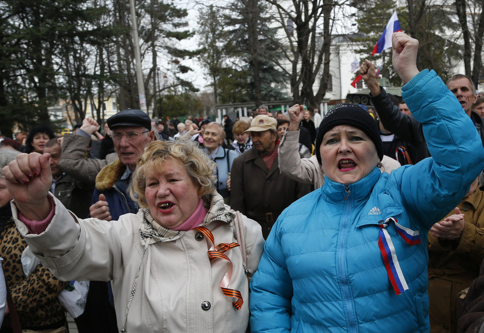 Photo - Pro-Russia demonstrators rally in front of the local parliament building in Crimea's capital Simferopol, Ukraine, Thursday, March 6, 2014. About 50 people rallied outside the local parliament Thursday morning waving Russian and Crimean flags. Lawmakers in Crimea called a March 16 referendum on whether to break away from Ukraine and join Russia instead, voting unanimously Thursday to declare their preference for doing so. (AP Photo/Sergei Grits)