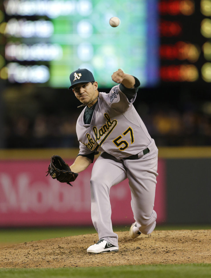 Photo - Oakland Athletics starting pitcher Tommy Milone throws against the Seattle Mariners in the third inning of a baseball game, Friday, April 11, 2014, in Seattle. (AP Photo/Ted S. Warren)