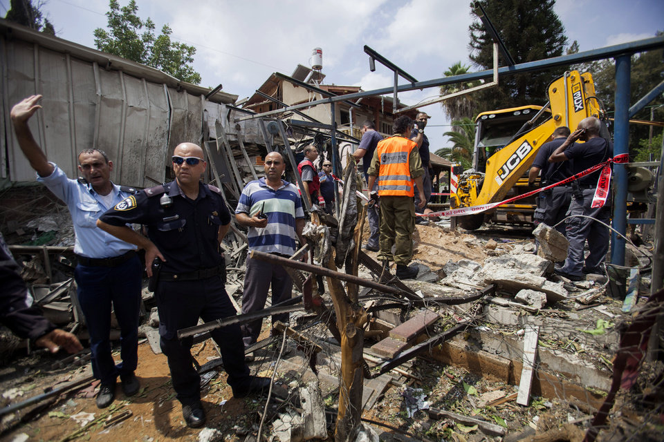 Photo - Israeli police officers secure a destroyed house that was hit by a rocket fired by Palestinians militants from Gaza, in Yahud, a Tel Aviv suburb near the airport, central Israel, Tuesday, July 22, 2014. As a result, Delta Air Lines and U.S. Airlines decided to cancel their scheduled flights to Israel.(AP Photo/Dan Balilty)