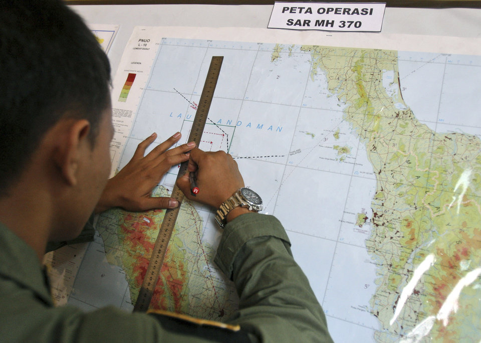 Photo - An Indonesian Air Force officer draws a flight pattern flown earlier in a search operation for the missing Malaysia Airlines Boeing 777, during a post-mission briefing at Suwondo air base in Medan, North Sumatra, Indonesia, Thursday, March 13, 2014. The hunt for the missing jetliner has been punctuated by false leads since it disappeared with 239 people aboard about an hour after leaving Kuala Lumpur for Beijing early Saturday. (AP Photo/Binsar Bakkara)