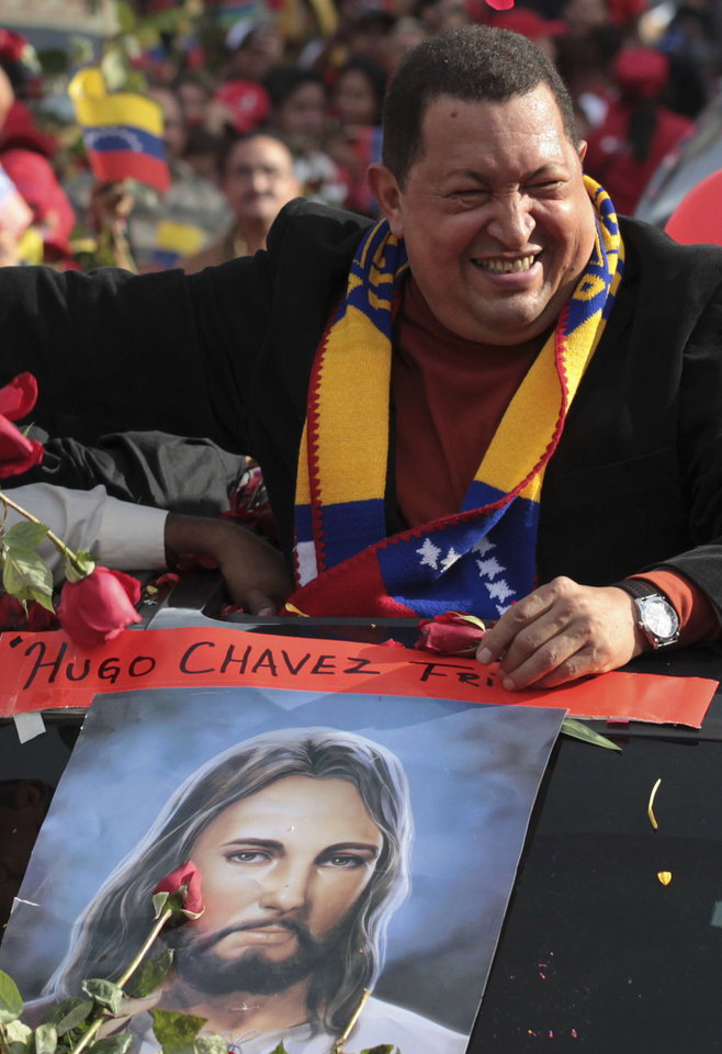 Photo -   FILE - In this Feb. 24, 2012 file photo, Venezuela's President Hugo Chavez greets supporters during his caravan from Miraflores presidential palace to the airport to travel to Cuba for surgery to remove a tumor, in Caracas, Venezuela. The poster shows an image of Jesus Christ. Chavez has spent much of his career praising the socialist ideas of famed atheists such as Karl Marx and Fidel Castro. However, now in the thick of a prolonged battle against cancer, Chavez is drawing inspiration more than ever from Jesus Christ. (AP Photo/Fernando Llano, File)