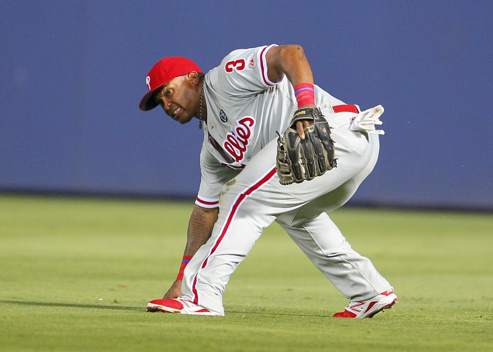 Photo - Philadelphia Phillies right fielder Marlon Byrd fields a ball driven to the outfield by Atlanta Braves Andrelton Simmons which advances Chris Johnson to third in the seventh inning of a baseball game Tuesday, June 17, 2014, in Atlanta. (AP Photo/Todd Kirkland)