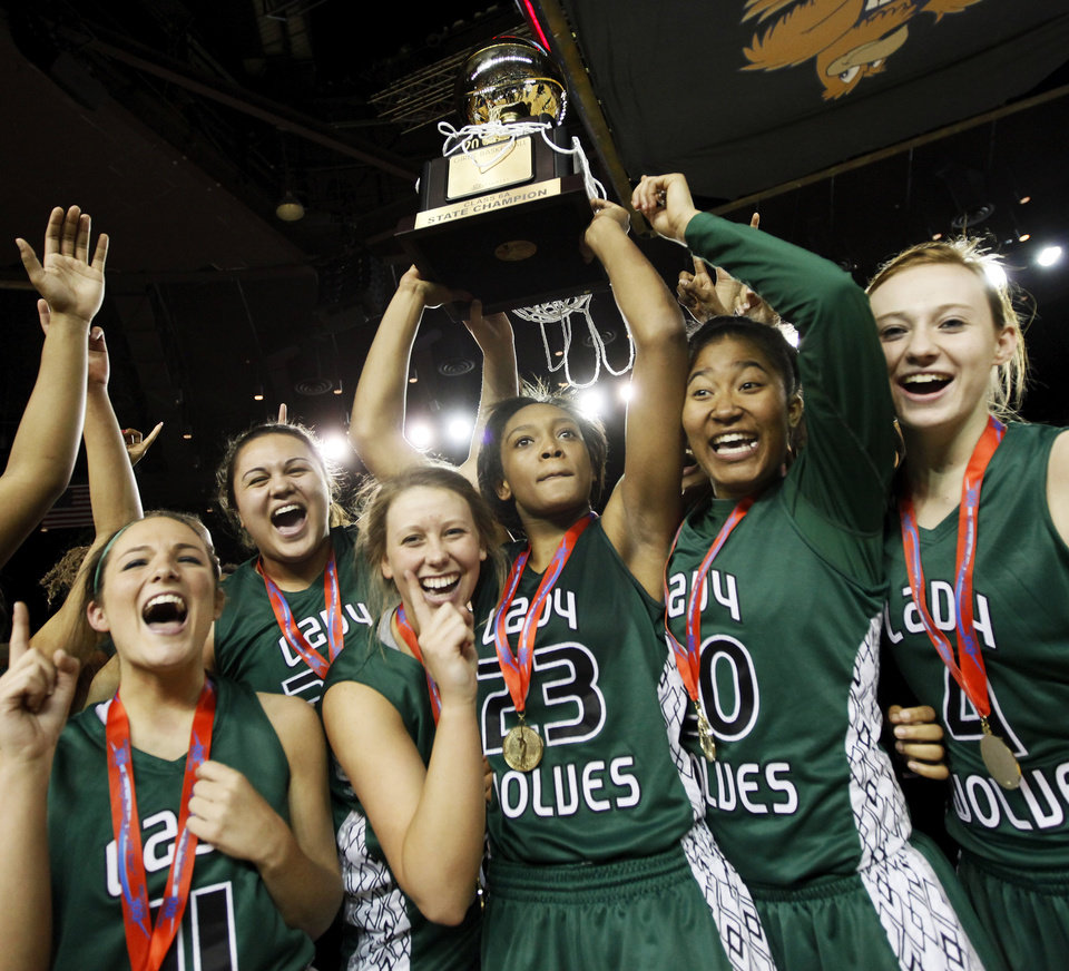 CELEBRATION: Courtney Walker (23) raises the gold ball championship trophy as the Edmond Santa Fe Lady Wolves celebrate after the Class 6A girls high school basketball state tournament championship game between Edmond Santa Fe and Edmond Memorial at the Mabee Center in Tulsa, Okla., Saturday, March 10, 2012. Santa Fe won, 44-41. Photo by Nate Billings, The Oklahoman
