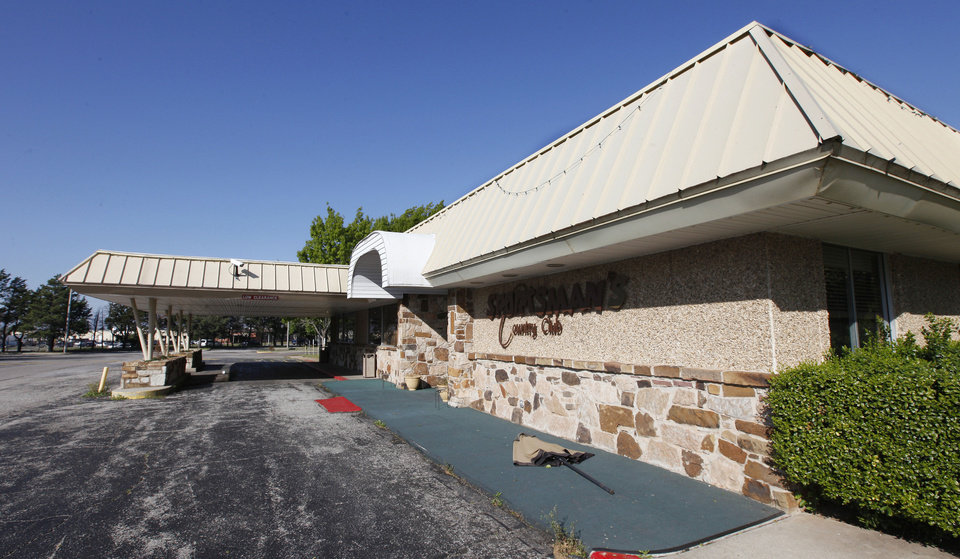Photo - Auctioneer Louis Dakil sold Sportsman's Country Club's property at auction Friday to investor Reza Mazrouee for $2.2 million. It included this 14,114-square-foot clubhouse and 50.7 acres with a lake.  PAUL B. SOUTHERLAND - The Oklahoman