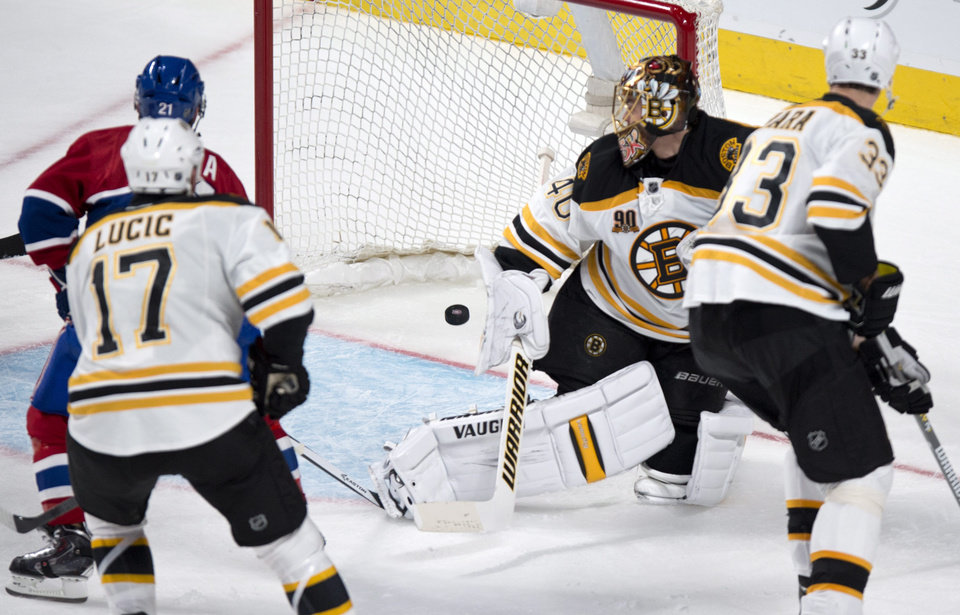 Photo - The puck goes into the net past Boston Bruins goalie Tuukka Rask on a goal by Montreal Canadiens' Tomas Plekanec as Milan Lucic, left, and Zdeno Chara look on during second period NHL hockey action Thursday, Dec. 5, 2013, in Montreal. (AP Photo/The Canadian Press, Paul Chiasson)