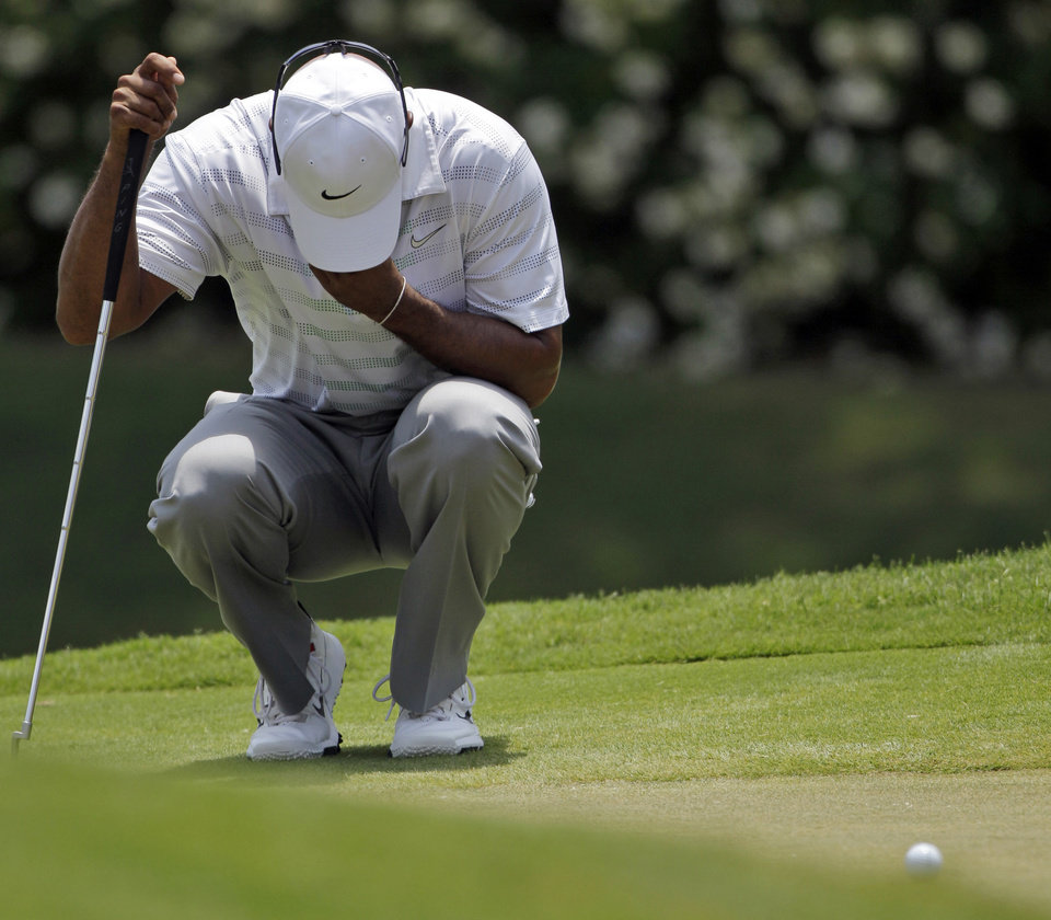 Tiger Woods bows his head while waiting his turn on the ninth green during the third round of the Players Championship golf tournament at TPC Sawgrass, Saturday, May 12, 2012, in Ponte Vedra Beach, Fla. (AP Photo/David Goldman)
