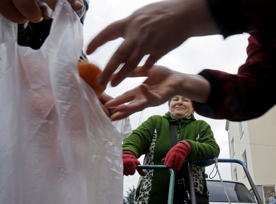 Photo - Mukhmunad Ashabokova watches as someone puts tangerines in a bag at the Abkhazian border Wednesday, Feb. 5, 2014, near Sochi, Russia. Most days in the tangerine season, she rolls her squat cart loaded down with the fruit across the bridge over Psou River from her garden about two miles inside Abkhazia. (AP Photo/Morry Gash)