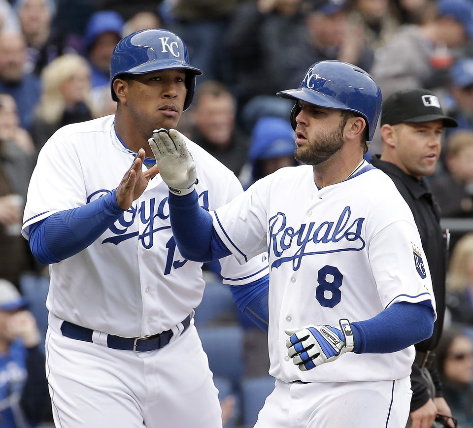 Photo - Kansas City Royals' Salvador Perez (13) and Mike Moustakas (8) celebrate after scoring on single hit by Lorenzo Cain during the fifth inning of a home opener baseball game against the Chicago White Sox, Friday, April 4, 2014, in Kansas City, Mo. (AP Photo/Charlie Riedel)