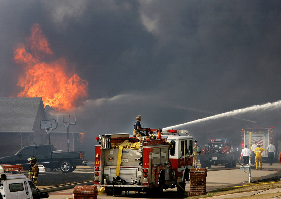 Photo - Firefighters battle homes on fire on both sides of  Westbury Street in the Oakwood East Royale neighborhood in Midwest City  Thursday, April 9, 2009.  Photo by Jim Beckel, The Oklahoman