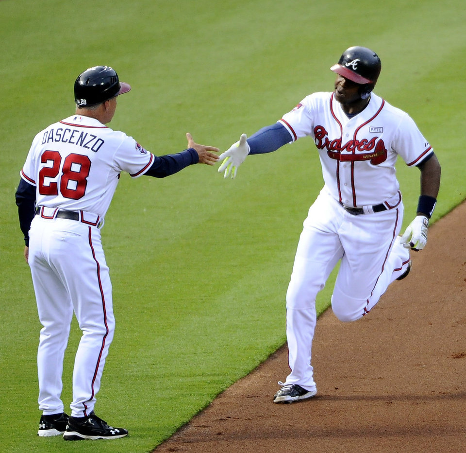 Photo - Atlanta Braves left fielder Justin Upton, right, is greeted by third base coach Doug Dascenzo (28) after Upton's two-run home run against the Washington Nationals during the first inning of a baseball game Friday, Aug. 8, 2014, in Atlanta. (AP Photo/David Tulis)