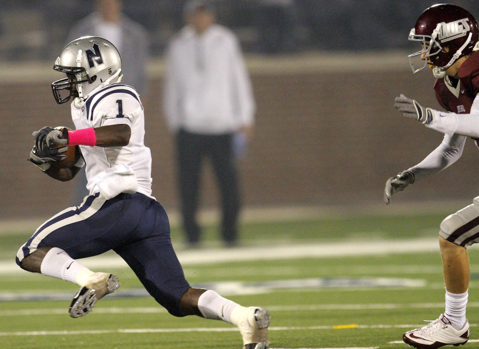 Photo - Edmond North's Jarion Tudman escapes an Edmond Memorial defender during the high school football game between Edmond North and Edmond Memorial at Wantland Stadium in Edmond, Okla., Friday, Sept. 16, 2011. Photo by Sarah Phipps, The Oklahoman