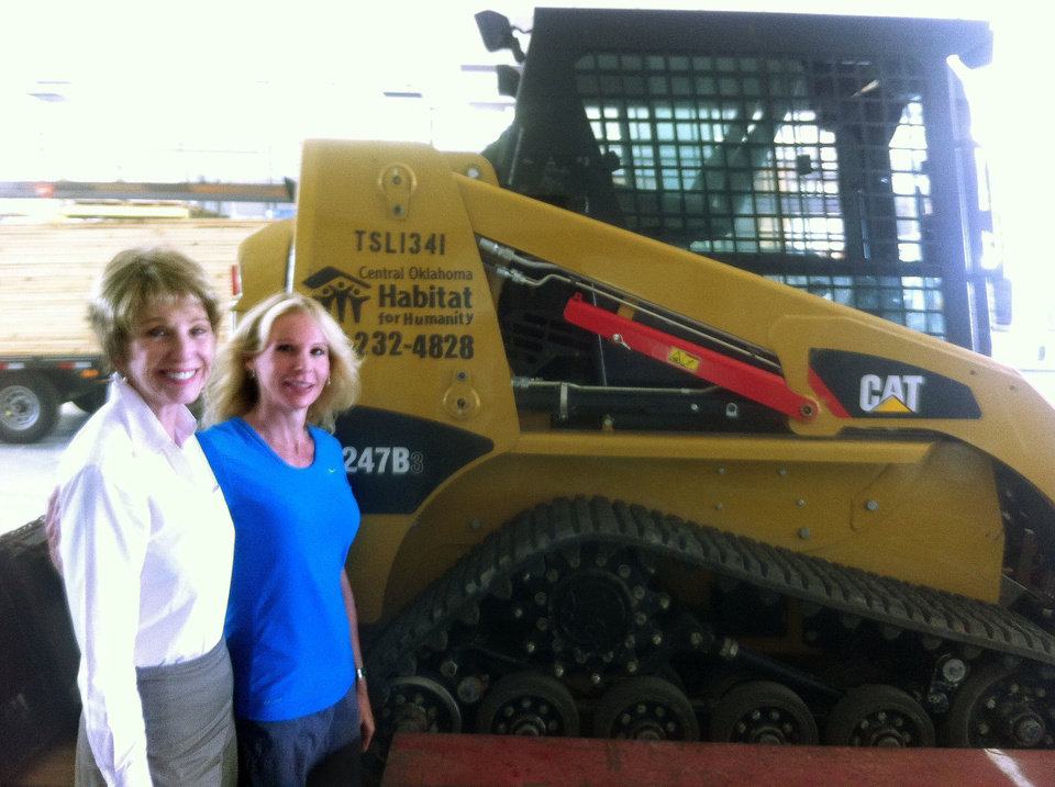 Photo - Ann Felton Gilliland, chairman and CEO of Central Oklahoma Habitat for Humanity, and Sharla Wilson, Habitat board member who also serves on the family selection committee, show off a recently donated front-end loader at Habitat's headquarters. 5005 S Interstate 35 Service Road. Central Oklahoma Habitat has helped in tornado recovery by taking down 40 several damaged houses.  Richard Mize - The Oklahoman