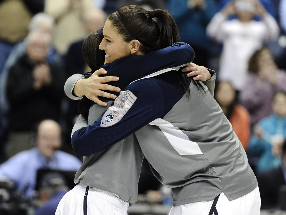 Photo - Connecticut's Bria Hartley, left, and Stefanie Dolson, embrace as they honored at senior night before an NCAA college basketball game against Rutgers, Saturday, March 1, 2014, in Storrs, Conn. (AP Photo/Jessica Hill)