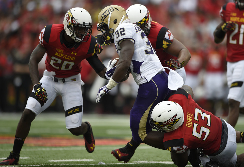 Photo - Maryland defensive back Anthony Nixon (20) and L.A. Goree (53) tackle James Madison running back Khalid Abdullah (32) during the first half of an NCAA college football game, Saturday, Aug. 30, 2014, in College Park, Md. Maryland won 52-7. (AP Photo/Nick Wass)