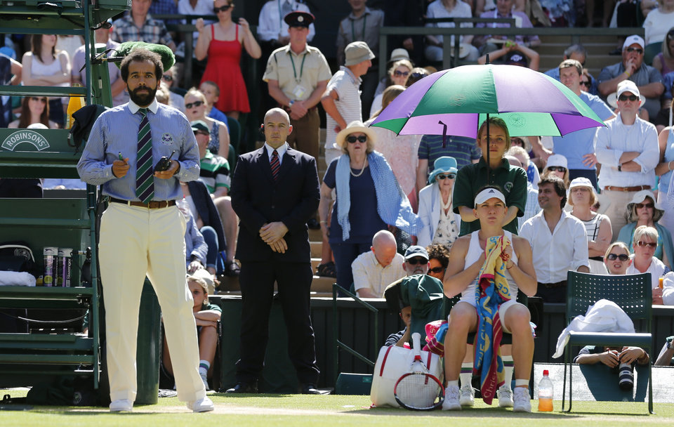 Photo - Umpire Kader Nouni, left, stands next to Simona Halep of Romania, sitting, during an interruption to take an ill woman from court during the women's singles semifinal match between Halep and Eugenie Bouchard of Canada at the All England Lawn Tennis Championships in Wimbledon, London, Thursday, July 3, 2014. (AP Photo/Ben Curtis)