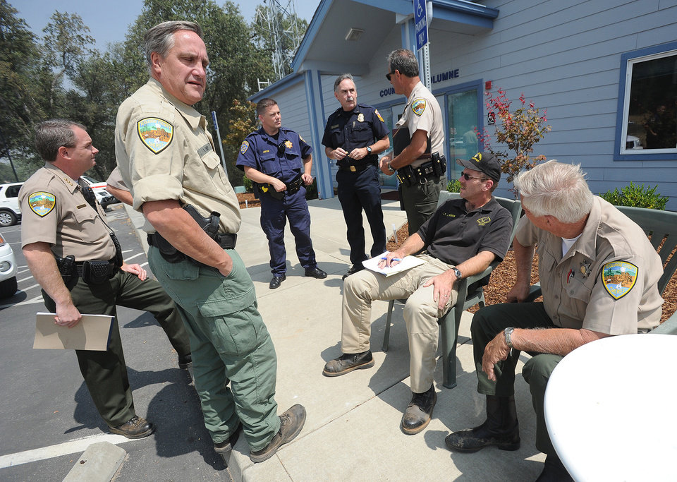 Tuolumne County Sheriff's convene at their command center between Tuolumne City and Sonora Saturday Aug. 24, 2013, as they continue to assist in road closures and protecting the homes of those who have evacuated Tuolumne City and surrounding communities. (AP Photo/The Modesto Bee, Elias Funez)