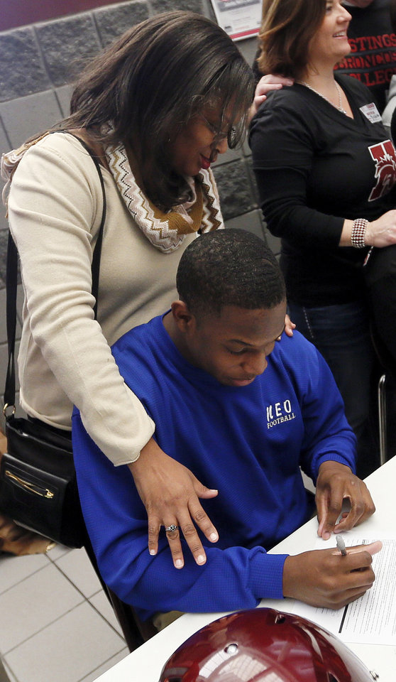 Ashton Antwine signs his letter to play football at NEO with his aunt Sonya Jefferson watching during signing day for student athletes at Edmond Memorial High School in Edmond, Okla., Wednesday, Feb. 5, 2014. Photo by Nate Billings, The Oklahoman