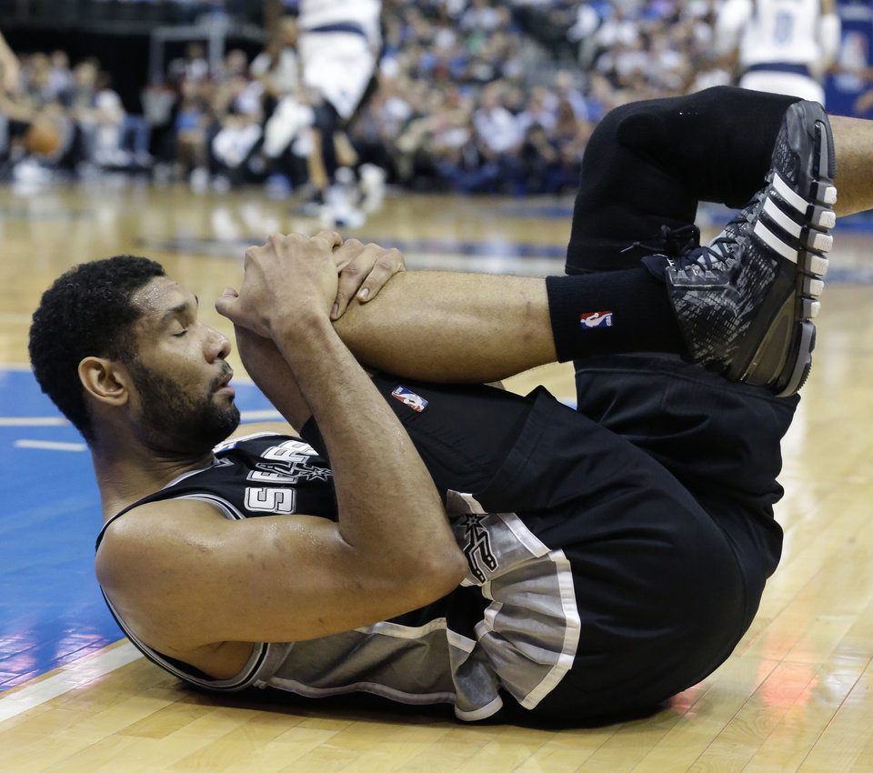 Photo - San Antonio Spurs forward Tim Duncan (21) holds his knee after landing hard during the first quarter of an NBA basketball game against the Dallas Mavericks on Thursday, April 10, 2014, in Dallas. Duncan left the court, but returned to the game later in the half. (AP Photo/LM Otero)