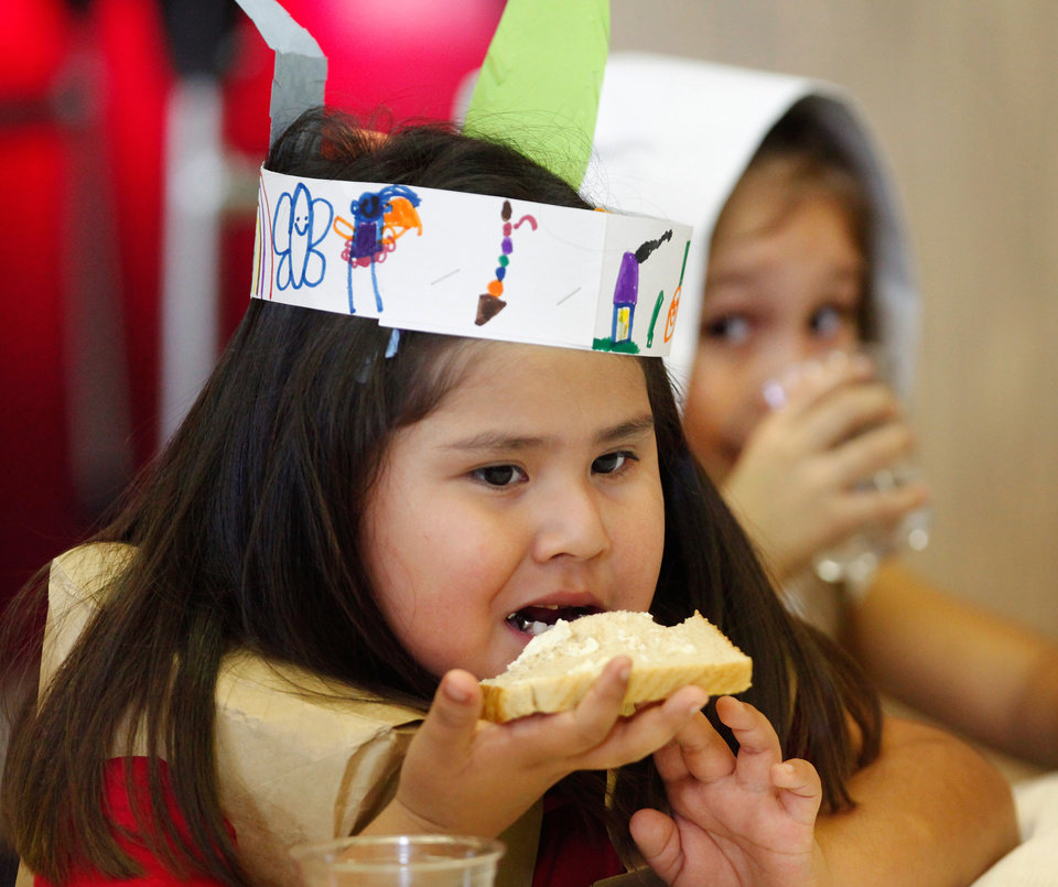 Photo - Nizhoni Gould, left, and Guadalupe Munoz represent the Indians and the Pilgrims at the Thanksgiving celebration.  Gould is eating bread topped with some of the homemade butter students made. Kindergarten students at Rancho Village Elementary School in southwest Oklahoma City dressed as Pilgrims and Indians and feasted on homemade butter they made in their classrooms earlier in the day. They also ate bread, celery and popcorn which the made in the cafeteria  Tuesday afternoon, Nov. 22, 2011.  Photo by Jim Beckel, The Oklahoman