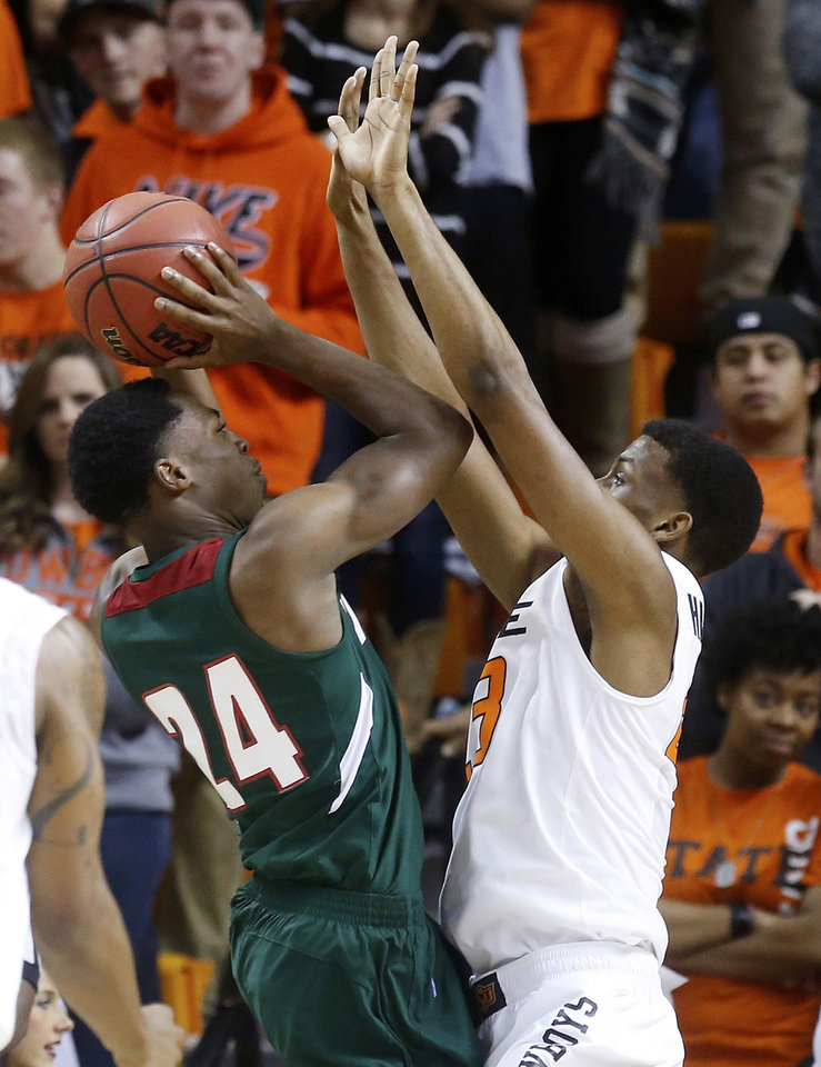 Photo - Mississippi Valley State guard Anthony McDonald (24) shoots as Oklahoma State wing Leyton Hammonds (23) defends in the first half of an NCAA college basketball game in Stillwater, Okla., Friday, Nov. 8, 2013. Oklahoma State won 117-62. (AP Photo/Sue Ogrocki)