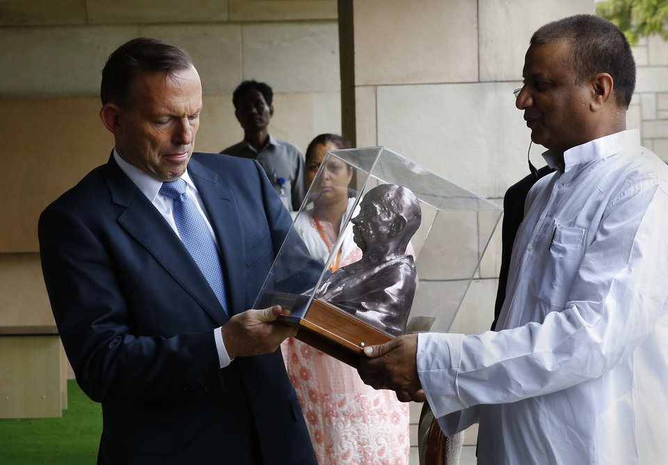 Photo - Australian Prime Minister Tony Abbott, left, is presented with a bust of Mahatma Gandhi at the Mahatma Gandhi memorial in New Delhi, India, Friday, Sept. 5, 2014. Abbott is on a two day visit to India. (AP Photo/Manish Swarup)